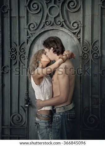 Young couple in love, kissing near vintage metal gate - stock photo