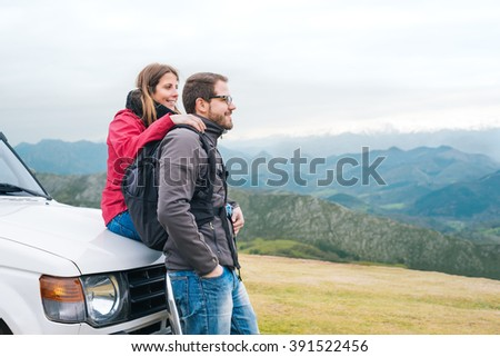 Young couple in love leaning on all terrain car, looking to the horizon, hiking outdoor on vacation, enjoying relaxing rural holidays. - stock photo