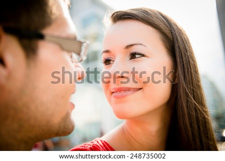Young couple in love looking to each others eyes - outdoor in street - stock photo