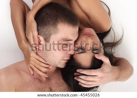Young couple in love lying down in white background - stock photo
