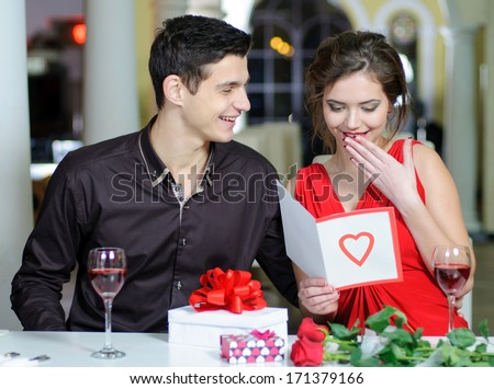 Young couple in love make a present to each other on Valentine's Day.