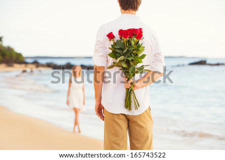 Young Couple in Love, Man holding surprise bouquet of roses for beautiful young woman, Romantic Date - stock photo