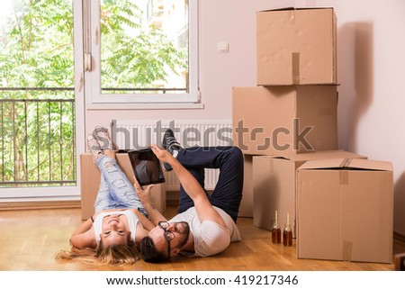 Young couple in love moving in a new flat, lying on the floor and surfing the web on a tablet computer in search of new redecoration ideas - stock photo