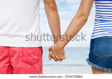 Young couple in love on the beach holding hands