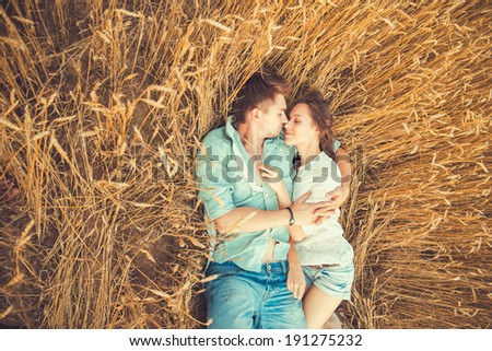 Young couple in love outdoor.in summer in field.Couple hugging.Young beautiful couple in love staying and kissing on the field on sunset. Soft sunny colors. Beautiful couple lying on the glass - stock photo