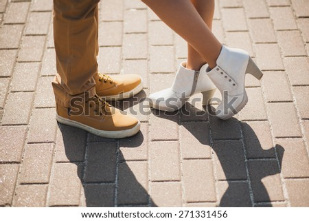 Young couple in love outdoor. Standing sensual woman and man.  Young stylish fashion couple posing in city street. Male and female legs. People in love. Casual bride groom. Wedding couple kissing - stock photo