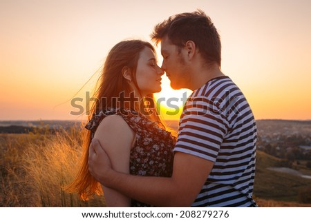 Young couple in love outdoor. Stunning sensual outdoor portrait of young couple posing in summer sunset in field - stock photo