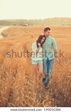 Young couple in love outdoor.Stunning sensual outdoor portrait of young stylish fashion couple posing in summer in  field - stock photo