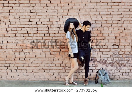 Young couple in love outdoor. Stunning sensual outdoor portrait of young stylish fashion couple posing near a wall - stock photo