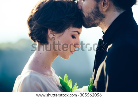 Young couple in love outdoor.Stunning sensual outdoor portrait of young stylish fashion couple posing in summer sunset. wedding style - stock photo