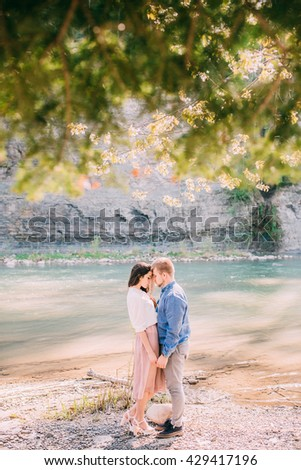 Young couple in love outdoor.Stunning sensual outdoor portrait of young stylish fashion couple posing in summer near the river