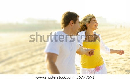 Young couple in love, playing together on the beach - stock photo
