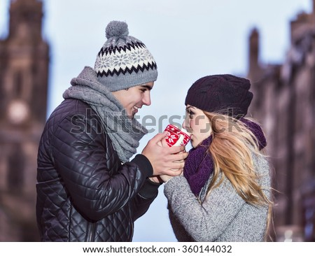 Young couple in love share hot drink in red cup on Royal Mile in Edinburgh. Two youngsters dating on Valentine's day - stock photo