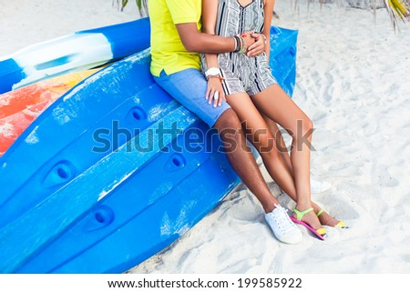 Young couple in love sitting at kayak blue boat at beach with white sand, wearing stylish clothes and enjoy their weekend with each other. - stock photo