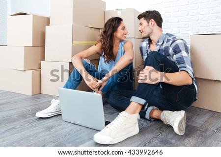 Young couple in love sitting on the floor of their new apartment using laptop - stock photo