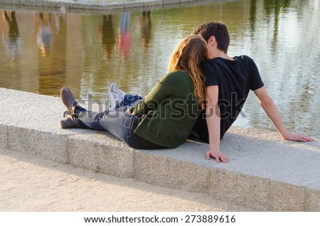young couple in love sitting on the park ground near the water. Summer is the best time for love - stock photo