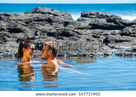 young couple in love spending time on the island Mauritius on the shores of the Indian Ocean. They take a sunbath on the rocks and swim the clear waters of small lakes - stock photo