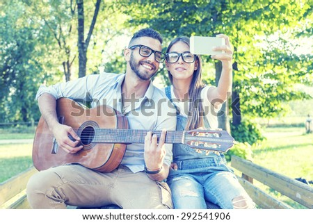 young couple in love takes a selfie while plays guitar - stock photo