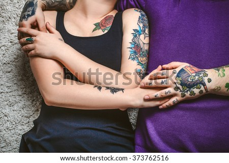 young couple in love, tattoos, cuddling and holding hands on the bed - stock photo
