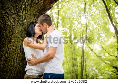 Young couple in love together in nature kissing at tree