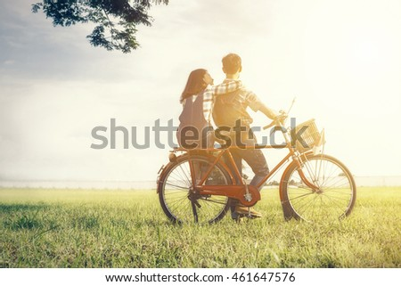Young couple in love, two lover as farmer with bicycle in love at meadow with vintage sunset lighting photography.