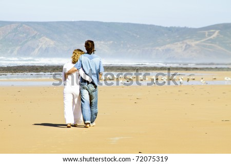 Young couple in love walking at the beach - stock photo