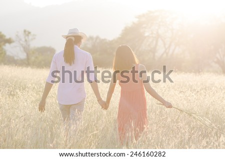 Young couple in love walking in the autumn field holding hands. In nature sun light. - stock photo