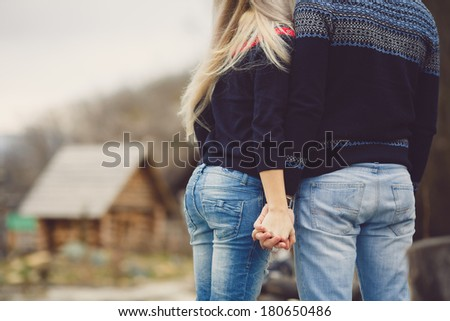 Young couple in love walking in the autumn park holding hands in hands - stock photo