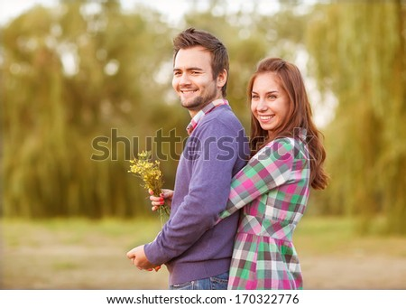 Young couple in love walking in the autumn park near the river. - stock photo