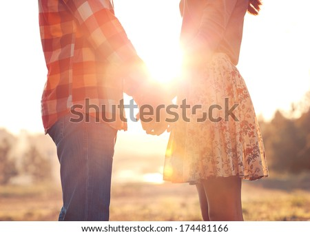Young couple in love walking in the holding hands looking in the sunset. concept of Valentine's Day. - stock photo