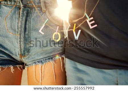 Young couple in love walking in the park holding hands looking in the sunset, words love, concept of Valentine's Day  - stock photo