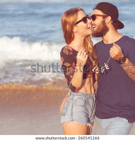 Young couple in love walking in the sea holding hands looking in the sunset, concept of Valentine's Day