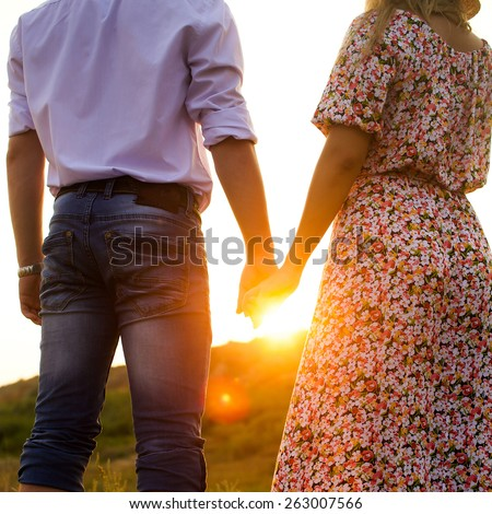 Young couple in love walking in the spring  park holding hands looking in the sunset.  warm sunny colors. - stock photo