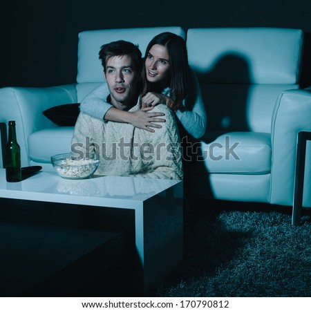 Young couple in love watching TV at night - stock photo