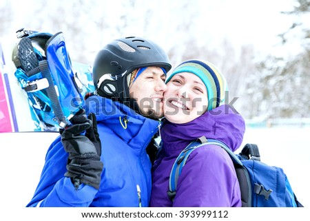 Young couple in love with snowboarding suits outdoors in winter on the mountain. Tender feelings with a smile and eyes. portrait of two young lovers with snowboard in the hands.