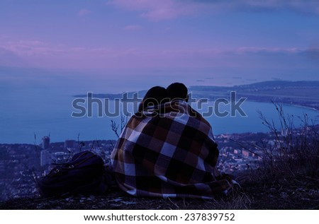 Young couple in love wrapped in plaid sitting on hill and looking at the city in night. Concept of tranquil life from the urban bustle - stock photo