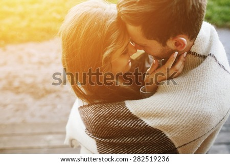 Young couple in love wrapped in plaid standing and looking at each other - stock photo