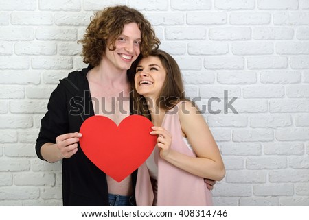Young couple in love. Young man and woman embracing and holding red paper heart - symbol of love.  - stock photo