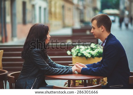 Young couple in lover staring at each other. In a coffee shop. - stock photo
