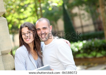 Young couple in public park with electronic tablet - stock photo