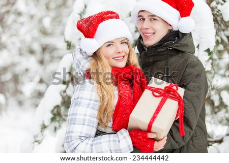 Young couple in santa claus hats holding gift over winter forest background - stock photo