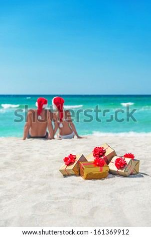 Young couple in santa hats at sea sand beach with christmas packed  golden gifts - stock photo