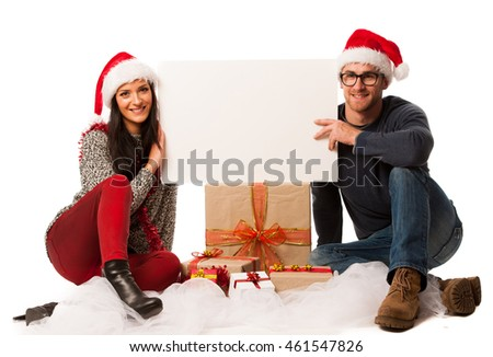 Young couple in santa hats holding blank board for advertisement. Invitation to christmas activities.