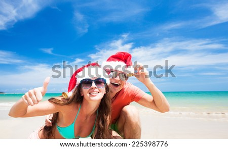 young couple in santa hats laughing on tropical beach. new year - stock photo