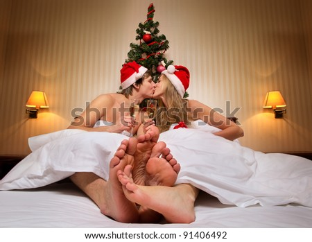 Young couple in Santa's hats  with glass of champagne kissing on bed with Christmas tree