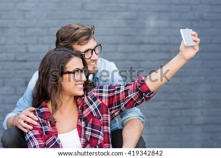 Young couple in spectacles taking a selfie on a mobile phone - stock photo