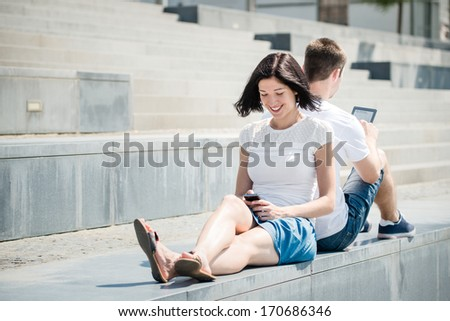 Young couple in street - woman with smartphone, man with tablet - stock photo