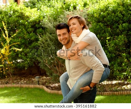 Young couple in the green. Man carrying girlfriend, having fun together, laughing. - stock photo