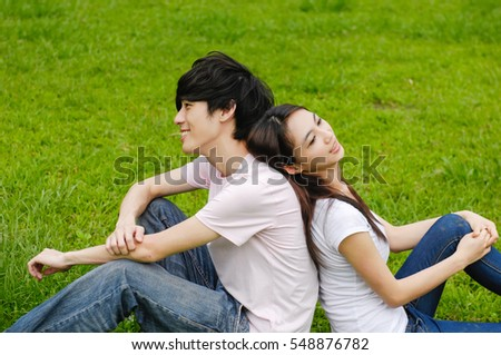 Young couple in the park sitting on the grass