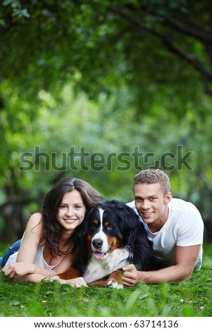 Young couple in the park with a dog - stock photo